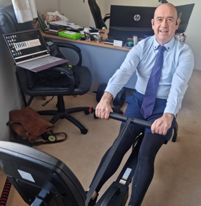 Garret Norris exercising on his rowing machine, half dressed in a shirt and tie and the bottom half in lycra spandex tights for lockdown work from home