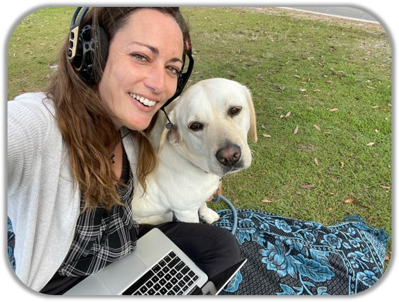 Maud Vanhoutte, KONA's Effective Communication Specialist, with her dog Nalla on a picknic blanket in the park with her laptop